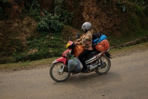 Woman driving a loaded motorbike