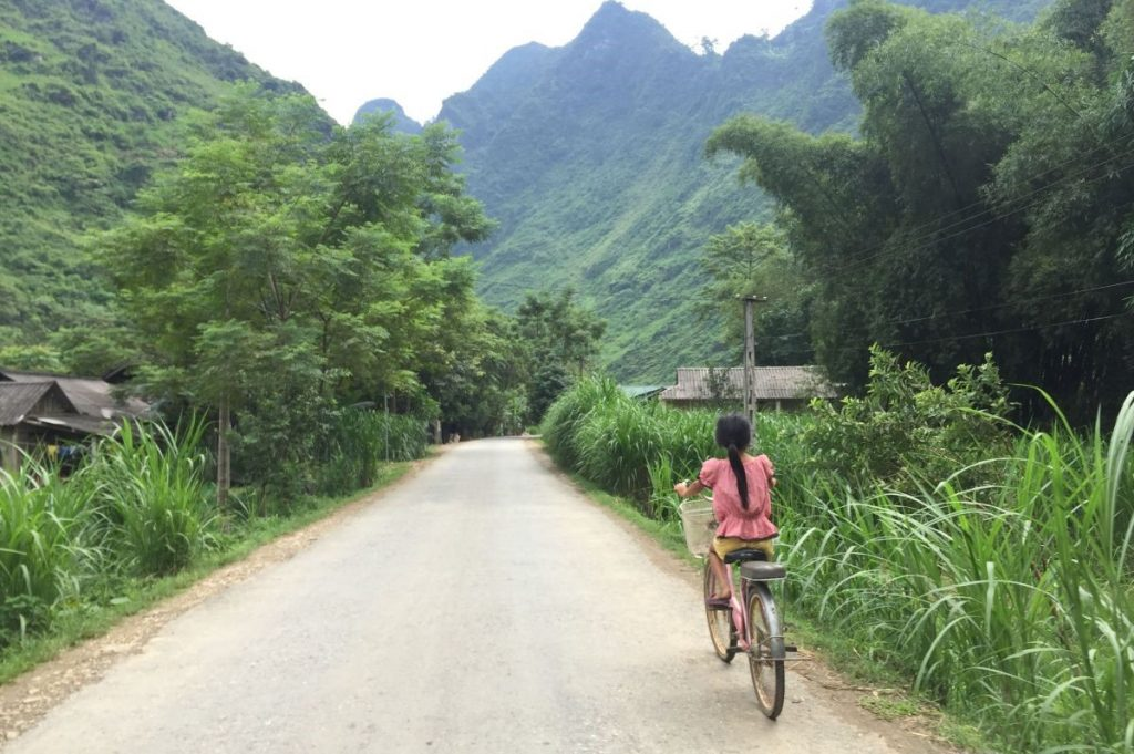 Young girl cycling on a small road in Ha Giang